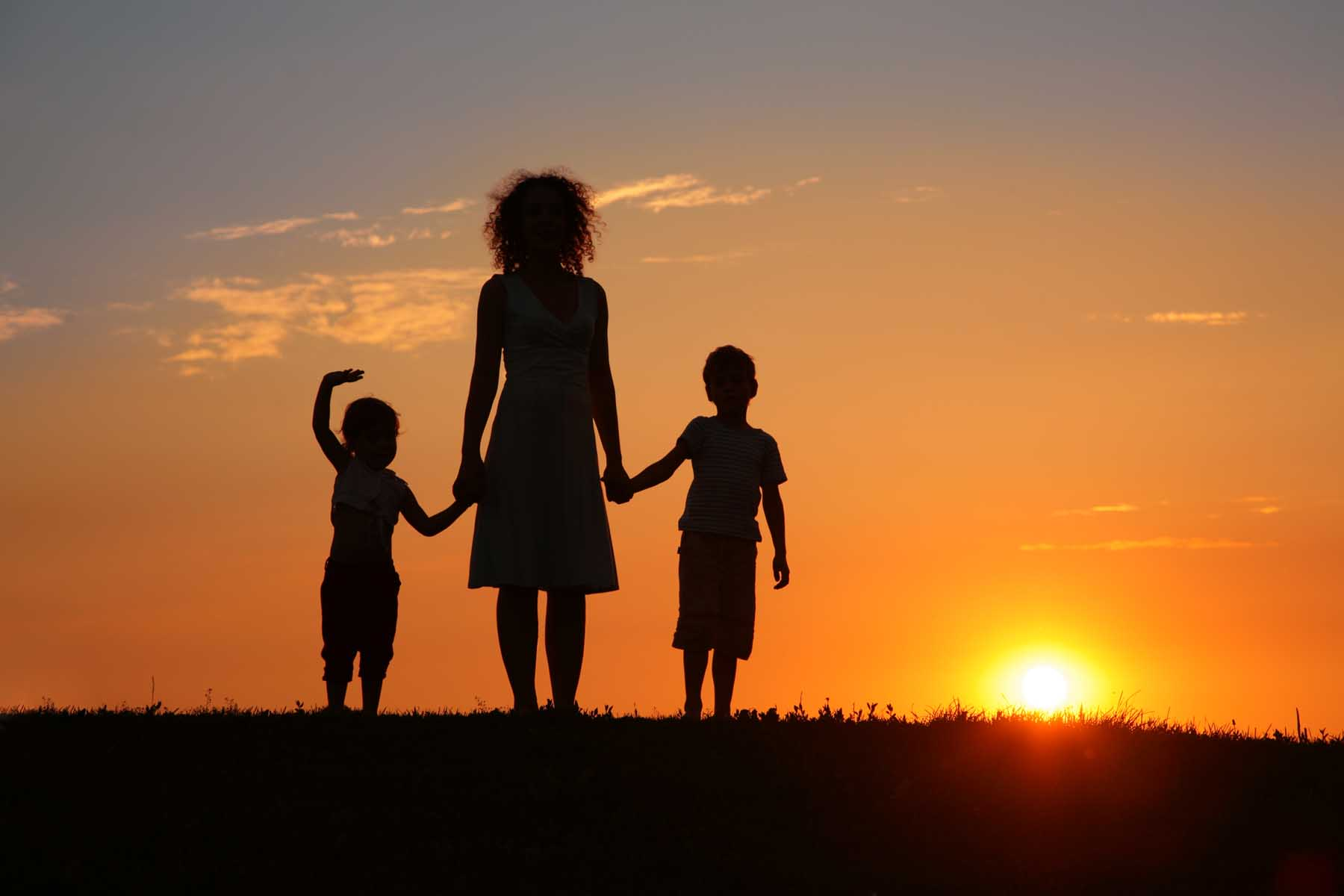 Mother and children facing the sunset